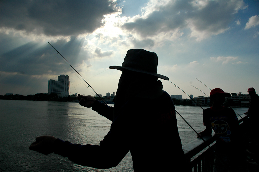 Residents fish on a bridge over Bangkok's Chao Phraya river.
