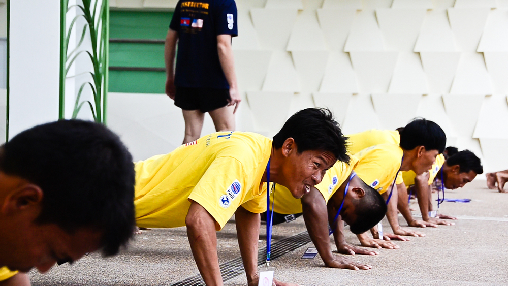 De-miners with the Cambodian Mine Action Centre (CMAC) do push-ups during land training for the country's first underwater UXO removal team.