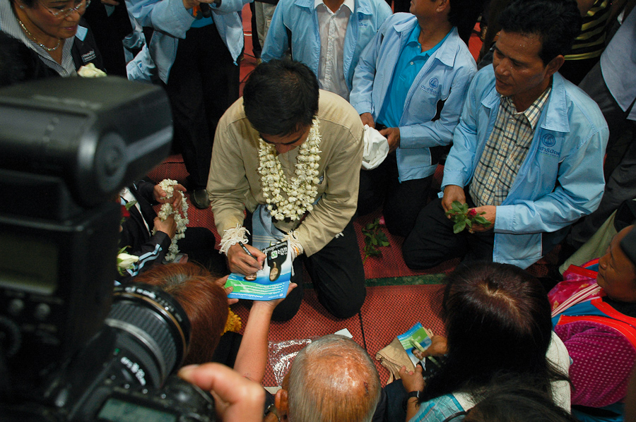 Thai Prime Minister Abhisit Vejjajiva signs autographs for party supporters at a campaign stop near Chiang Mai, Thailand.
