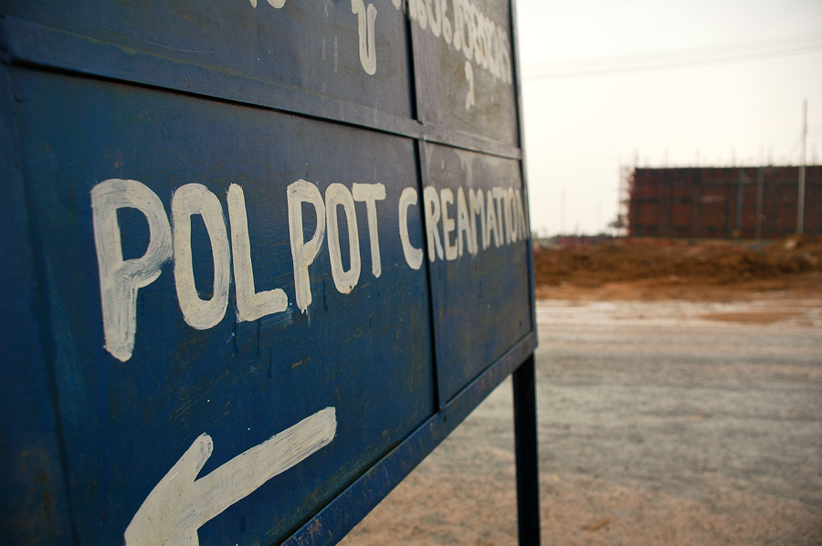 A road sign marks the location of Pol Pot's grave, near Anlong Veng, Cambodia. Across the street, a new casino development is under construction.