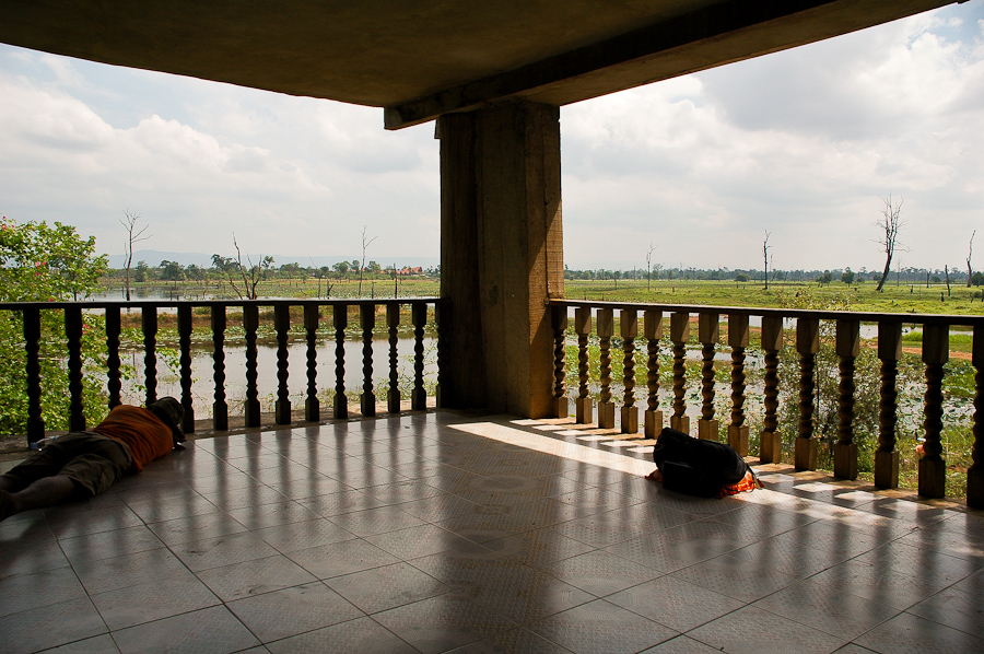 A visitor rests in the headquarters of former Khmer Rouge official Ta Mok, in Anlong Veng, Cambodia. The building is perched over a man-made lake. Most of the trees in the lake have died.