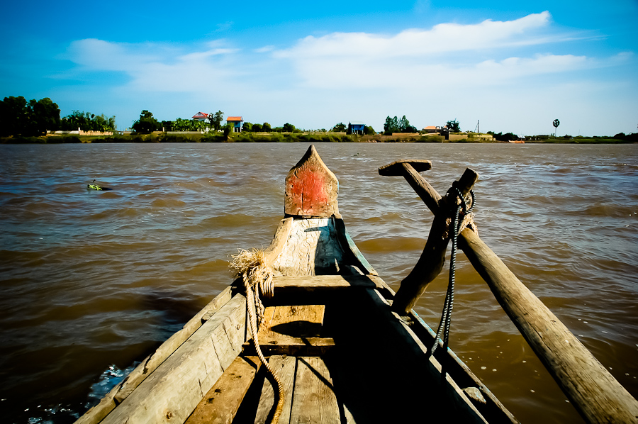 A fishing boat points toward the shore of the banks of the Tonle Sap, a Mekong tributary.