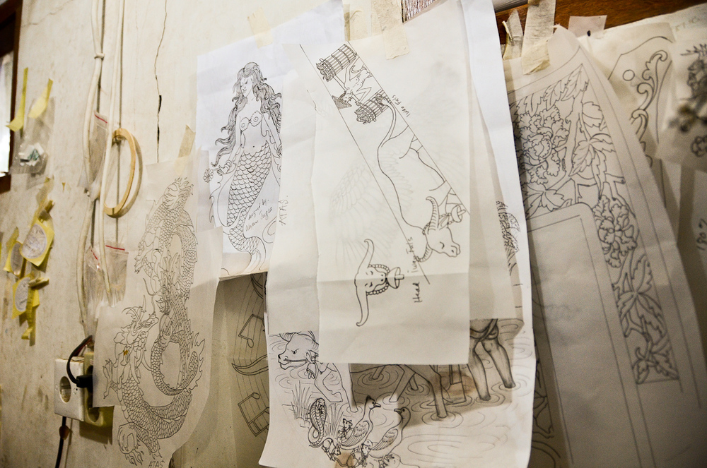 Sketches for designs that will decorate future guitars are taped to the walls of Wayan Tuges's Bali workshop.