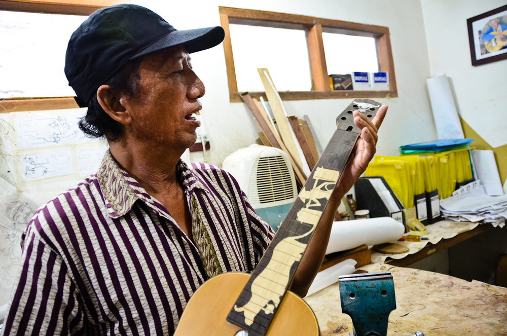 Wayan Tuges inspects a work in progress at his Bali guitar workshop.
