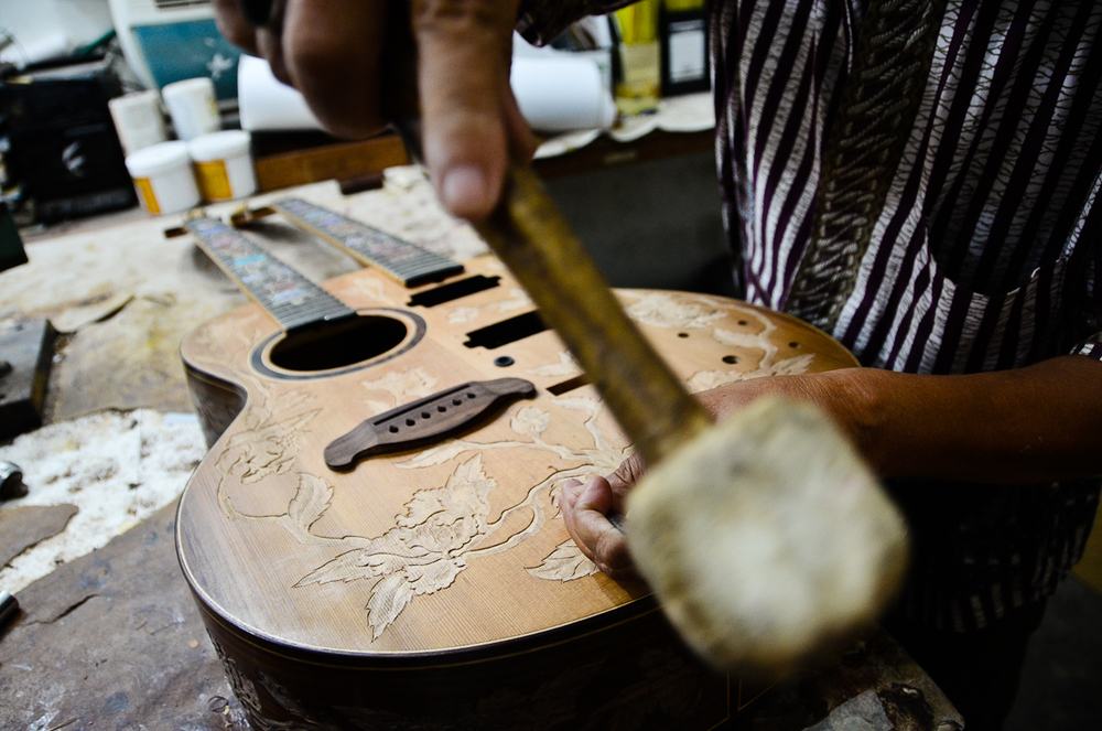 Wayan Tuges uses a mallet and chisel to etch a pattern into the face of a new guitar.