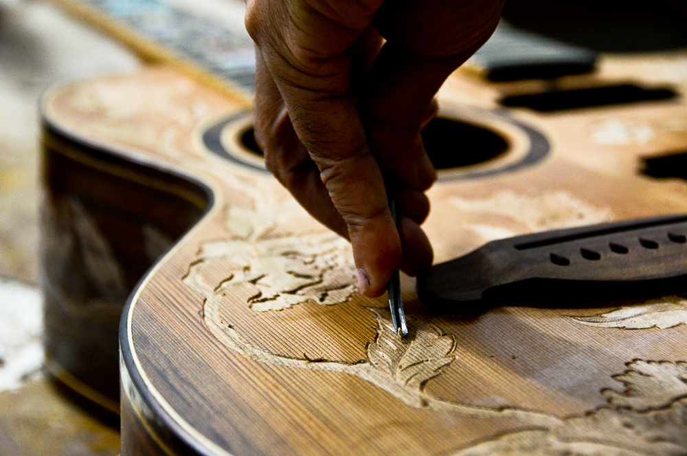 Wayan Tuges uses a chisel to etch a pattern into the face of a new guitar.