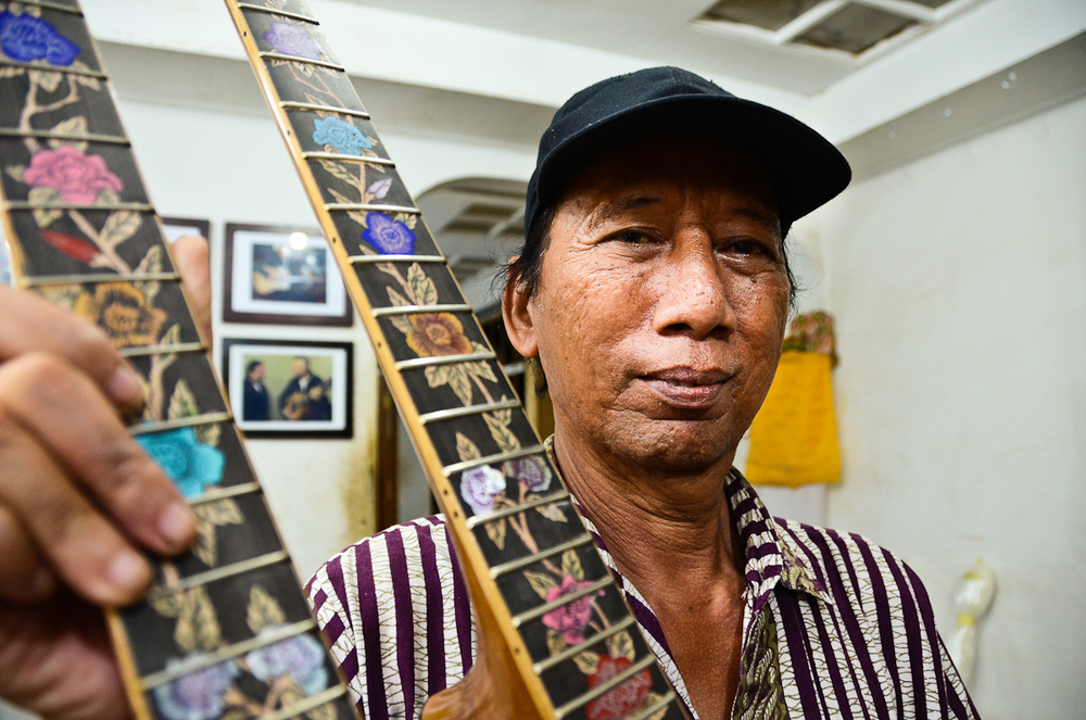 Wayan Tuges holds up a prototype for a new guitar: a double-necked acoustic/electric hybrid.