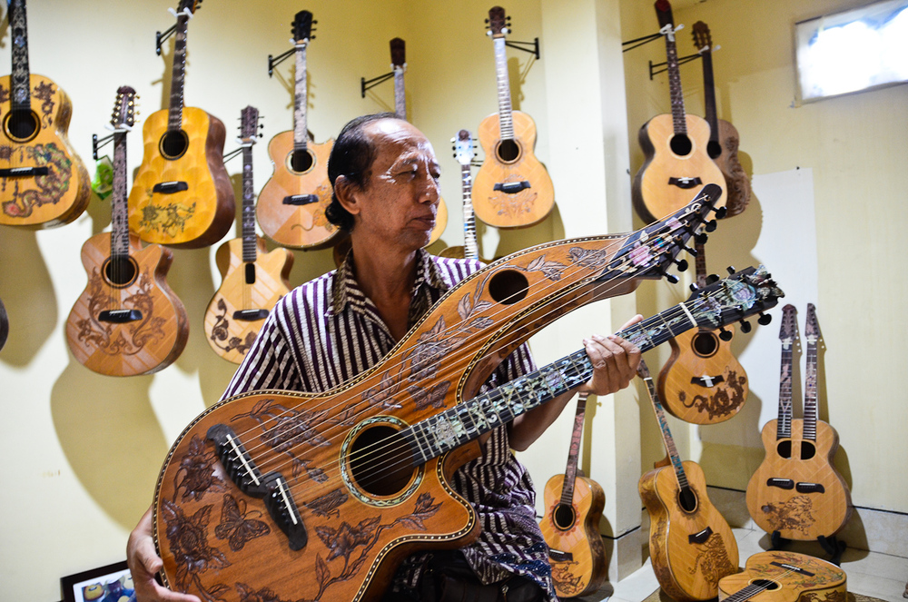 Wayan Tuges holds up a double-necked guitar in his workshop storage room.