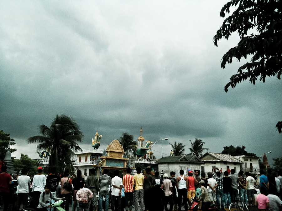 A storm cloud hovers overhead as protesters and onlookers gather outside a polling station in Phnom Penh.