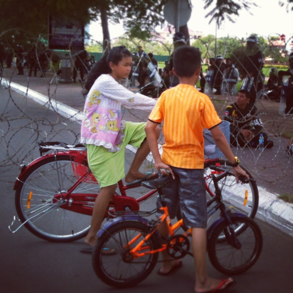 Children play by a barbed wire fence in central Phnom Penh.