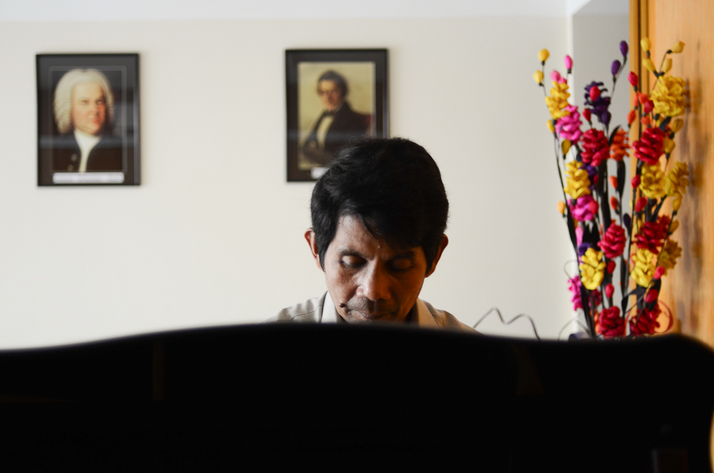 Him Sophy plays the piano at his studio in Phnom Penh.