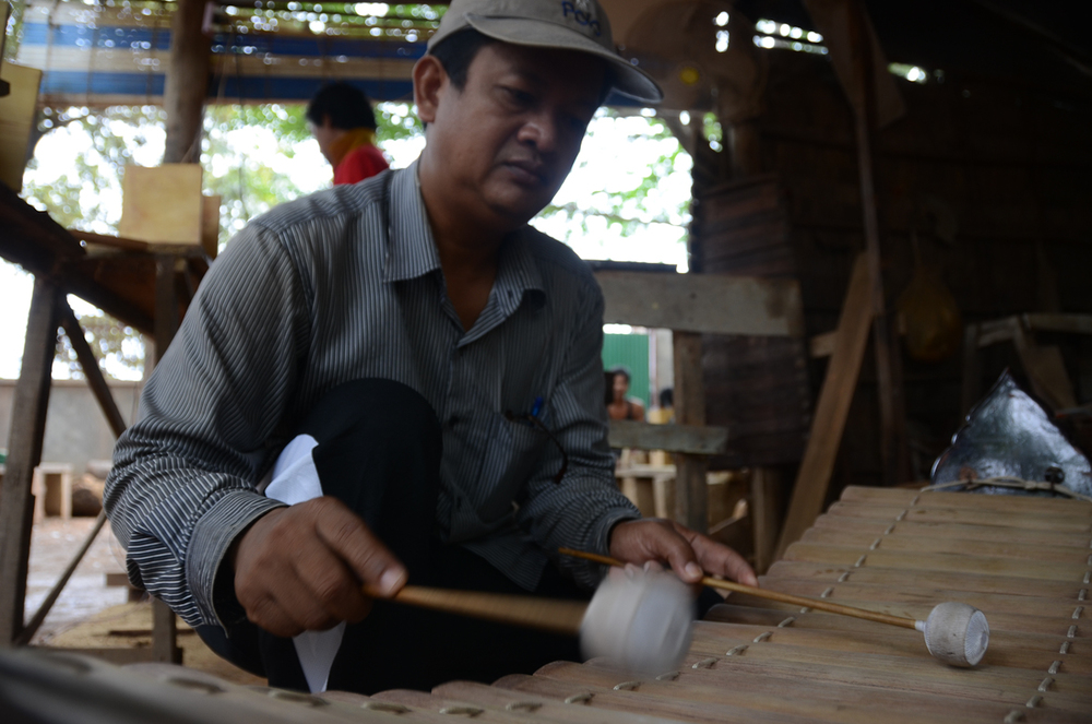 Keo Sonan Kavei plays the roneat, a type of Cambodian xylophone, at his instrument workshop near Phnom Penh.