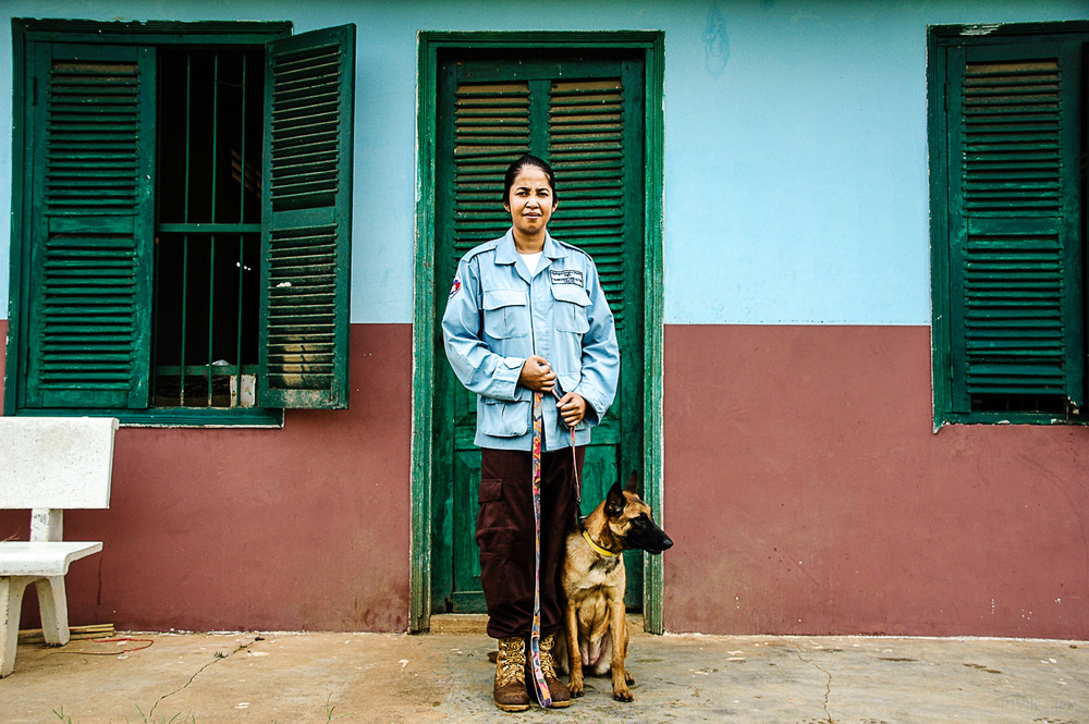 Suos Somaly stands with Sambath, a six-month-old puppy training to become a de-mining dog.