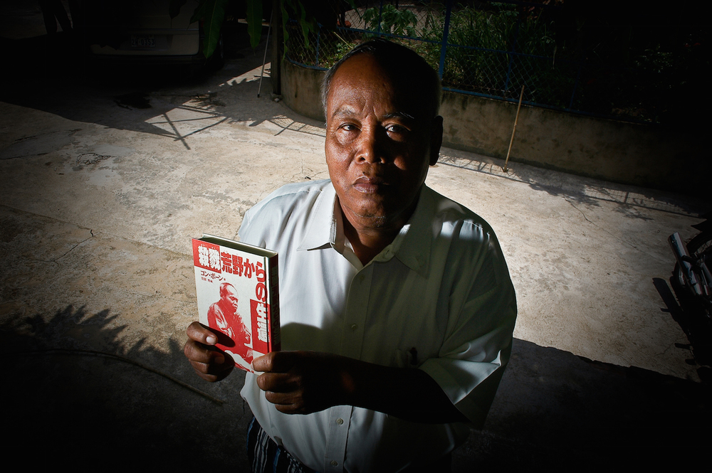 Kong Vorn, holding a copy of his Japanese-language memoirs, pictured at his Phnom Penh home in 2010.