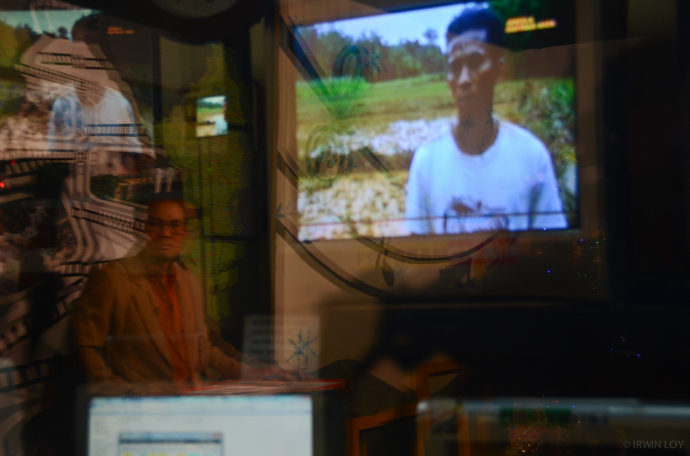 Alim, a journalist at RuaiTV, watches the screen as a pre-recorded TV package plays during the evening newscast, which he hosts.
