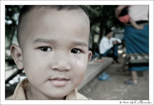 L aotion child on the street in Luang Prabang by Neil Alexander