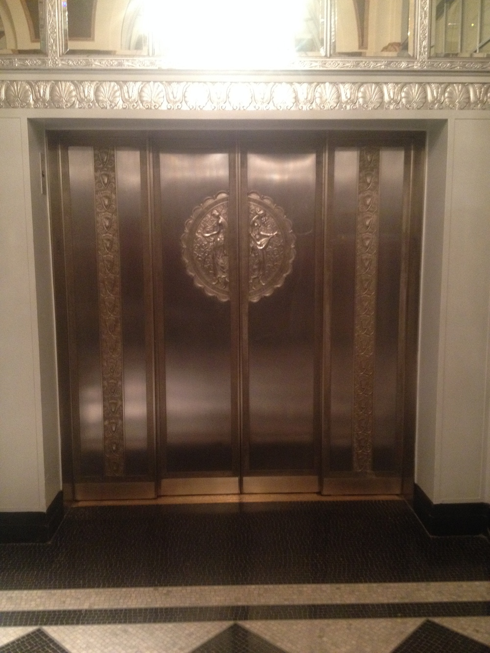 A discounted stay at the Waldorf Astoria.  Here are doors to one set of elevators.
