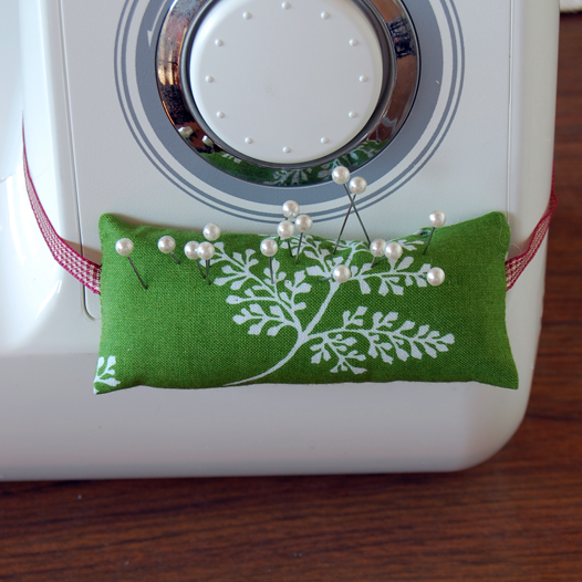 I like to take pins out just before I sew, rather than mowing over them.  This pincushion tied to my sewing machine makes sure those pins ain't goin' nowhere!