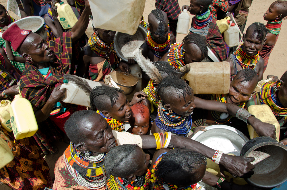 Villagers in Turkana, Kenya scramble to fill jugs of water from a 25,000 liter water truck that comes two times per week. Each family has a ration of 20 liters of water, but ideally they should have 100. The water truck is a temporary intervention while the a water pipeline is being built to bring water to Lopii.