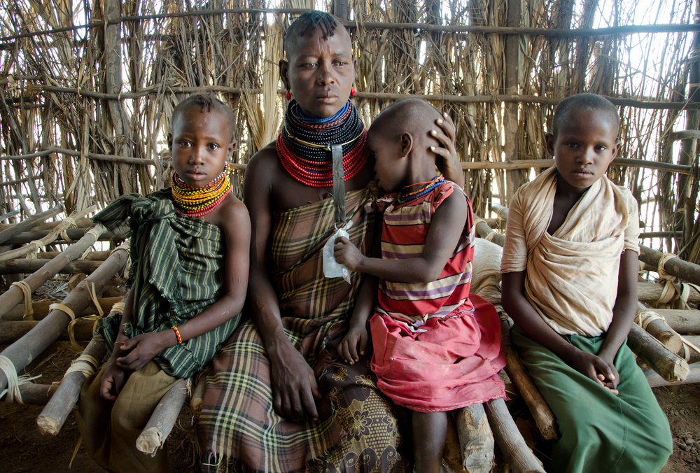 ​Emuria, 39, at a food distribution with three of her five children in Turkana, Kenya. Emuria's husband was shot in a cattle raid a little more than two years ago, leaving her to provide for the children on her own. All of their camels, cows, and goats were stolen in the raid.