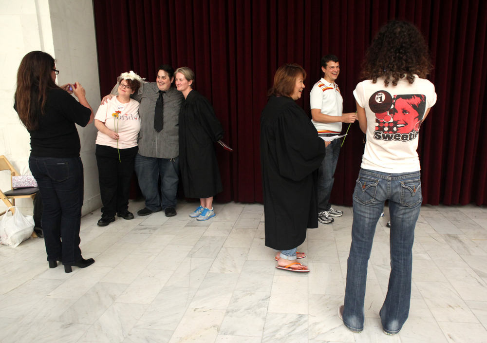 "The scene at City Hall was multiple couples getting married simultaneously wherever they could find floor space to stand and face each other. There were many Deputy Marriage Commissioners, dressed in black robes, spaced around the room waiting to declare ""spouses for life."""