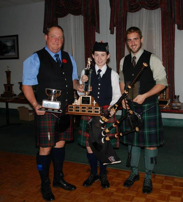 Sarah accepting her awards for 2012 Grade 1 Overall Champion Supreme and Grade 1 Piobaireachd from Chief Steward Rick Crawford (l) and ACPBA President David Kershaw (r)