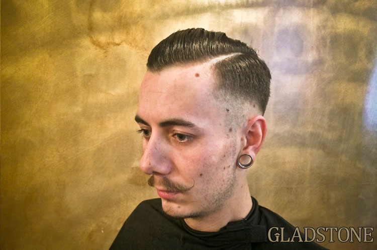 Here's Sam Pedder with a nice Ricki Hall inspired cut. A nice low skin fade, left heavy in the sides for the desired contrast. The hair is left heavy in the front to allow it to sit right back and finished off with a hard razor parting. Best product for a cut like this is a proper pomade to give that real slick look.