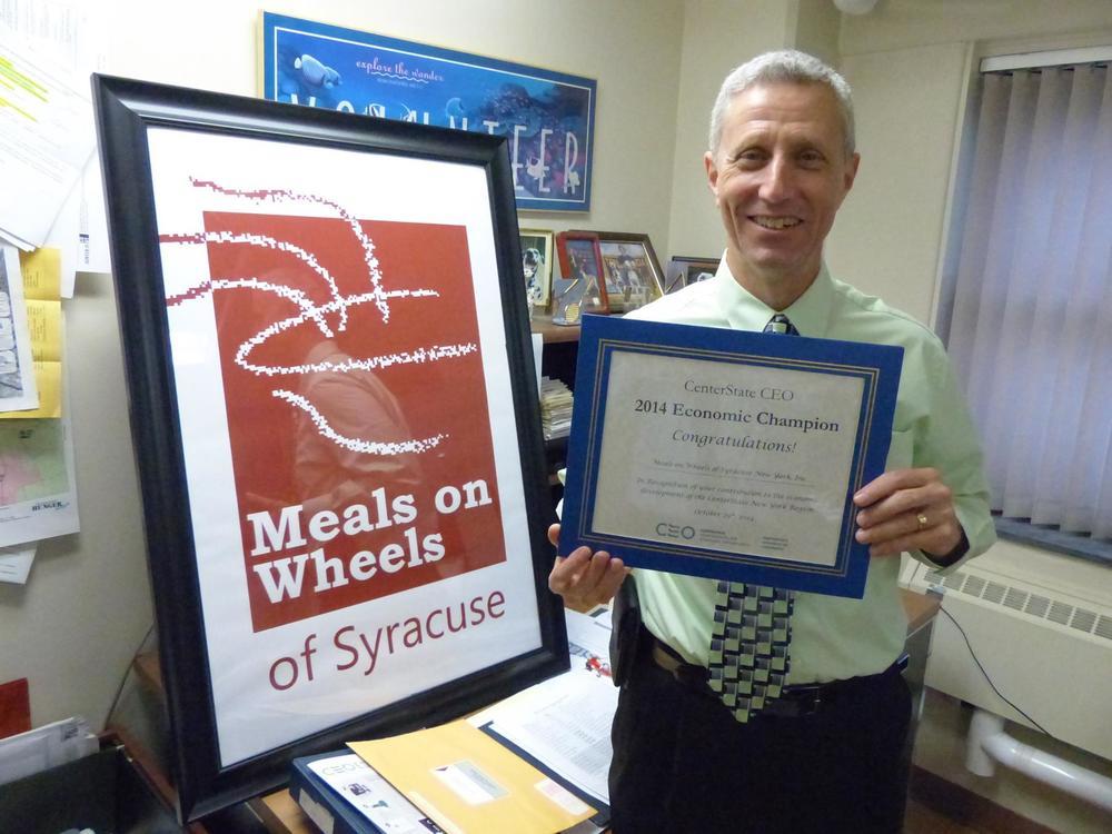 Mason Kaufman, Executive Director, holding 2014 Economic Champion award.