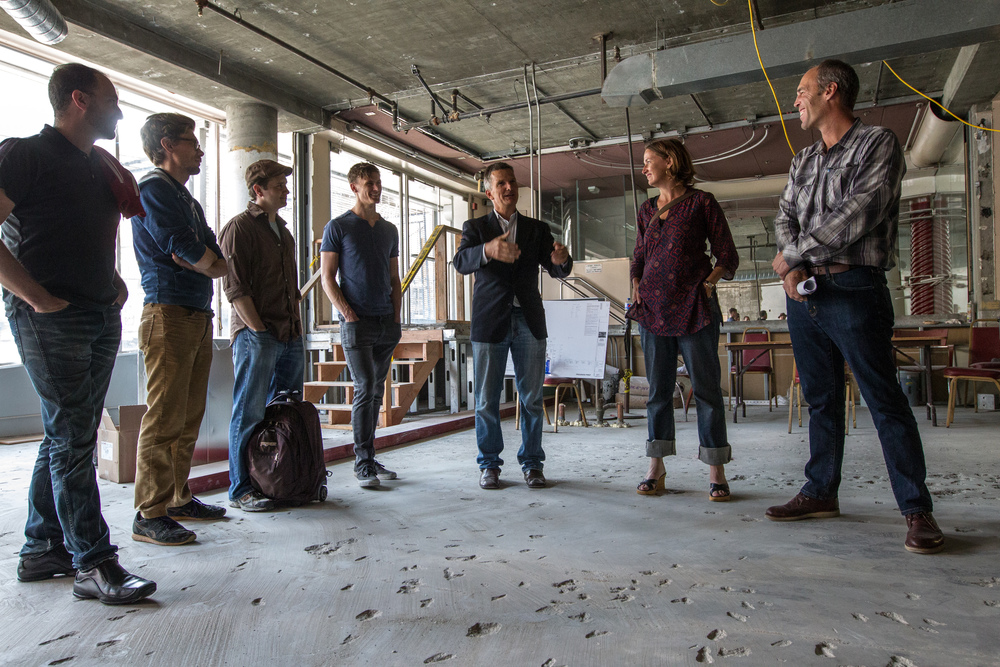 Property developer Chris Wight (center) discusses renovations with FilmHouse residents, Filmmaker360 Director Michele Turnure-Salleo, and Cypress Properties Group colleague Jeff Lee. Photo by Erin Lubin.