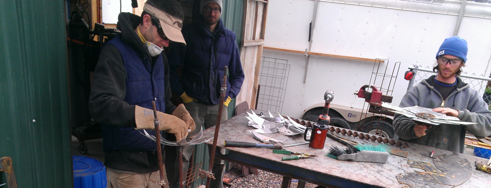 Wiley (Center), supervises Russell and Kevin on their Metal Flower Construction
