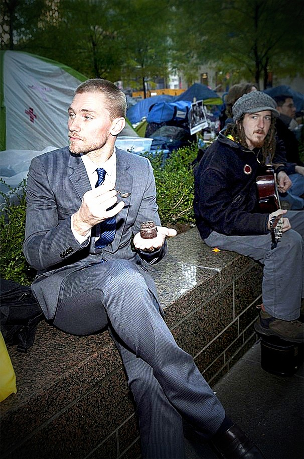 "Harvard MBA enjoys his lite lunch in Zuccotti Park as OWS protester plays ""Dust in the Wind."" (Credit: Reddit.com)"
