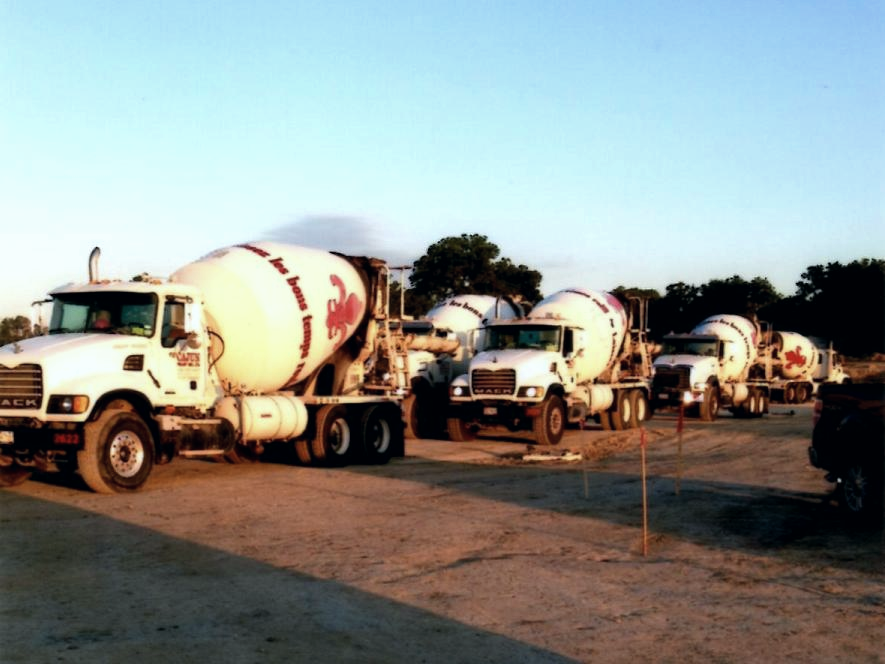 A few of Cajun Ready Mix Mixer Trucks delivering on site