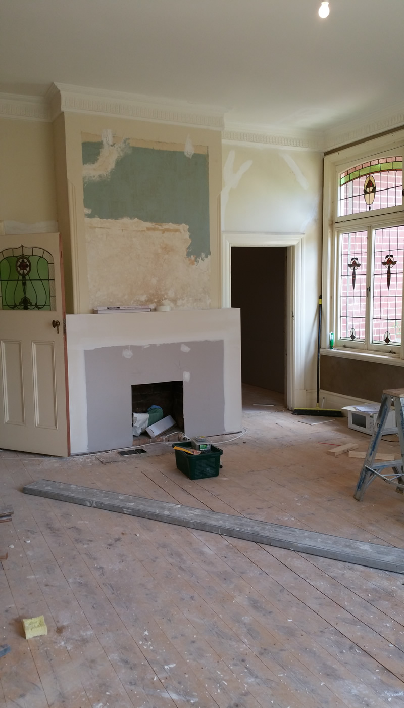 1980s travertine mantle has been removed and the beginnings of a new, much simpler mantle have been built, in better proportions with the room and windows.