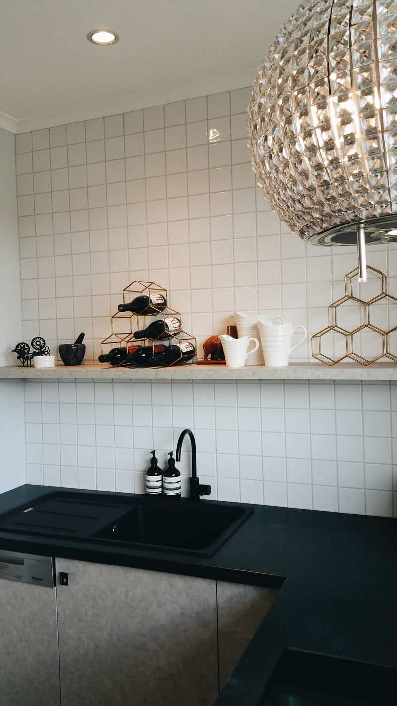 Honed black Indian granite, New Age Veneer cupboards in a mottled grey tone, simple square rippled white wall tiles and a matt black mixer from Brodware create a monotone backdrop for whatever my client may want to put on display on her open shelf. Each time I visit, there is something new!