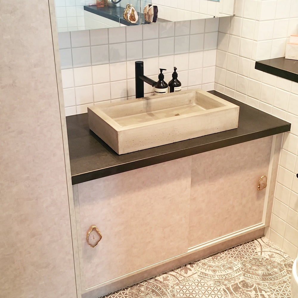 CONTRAST OF TEXTURE - A hand made concrete basin contrasts with the perfectly smooth Indian Granite bench on which it sits.Handles of randomly cut agate contrast with the intricate hexagon tiled floor.