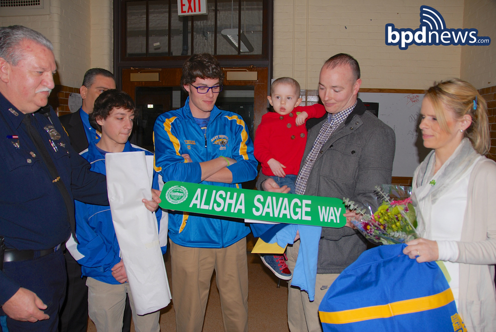 Boston Police Officer Bobby Anthony presents alisha savage and her family with a boston street sign commemorating today's check presentation