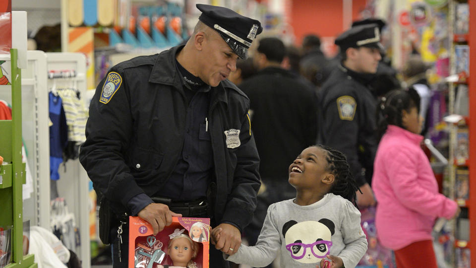 SANTAS IN BLUE: Officer Jorge Dias helps Janiyah Woodley, 7, carry her new doll at the Dorchester target yesterday. (photo by Chris Evans)