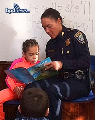 Deputy Baston reading to a first-grader at the Pope John Paul II Catholic Academy
