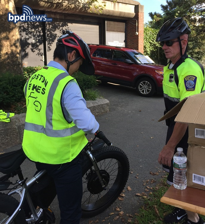 Keeping Boston Safe:  Officers from District E-13 hand out 200 free bright-yellow bike vests to bikers in Jamaica Plain