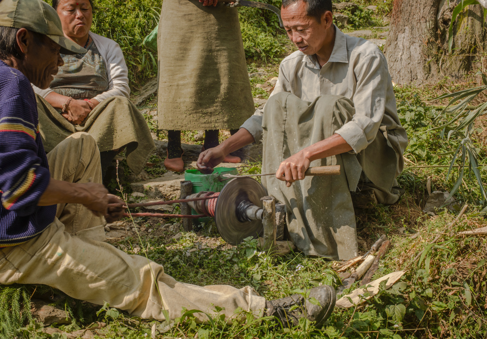 Men sharpen the knives used for pruning in the tea plantation. The grinding wheel is driven by pulling back and forth on a rope wrapped around a drive spindle.