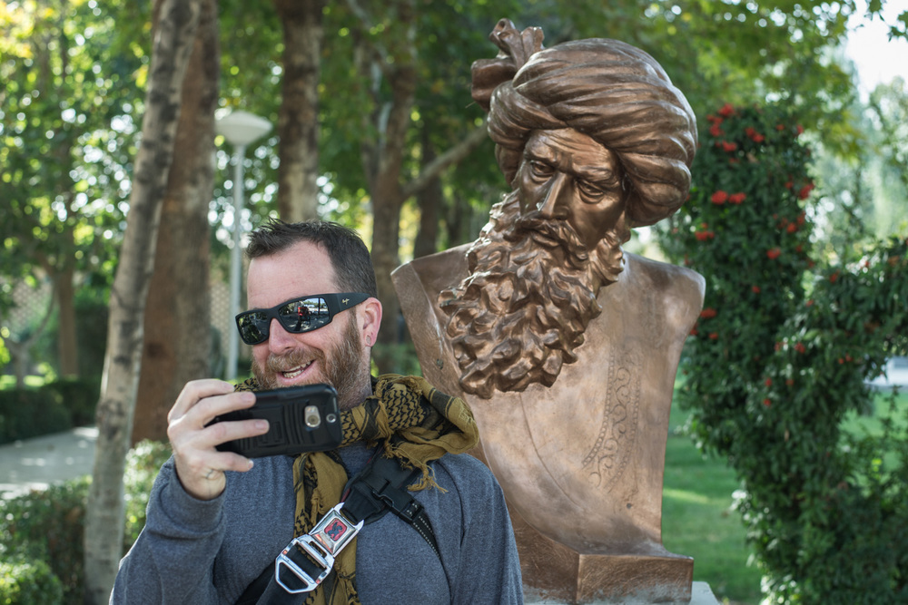 Tourist doing a selfie of himself with statue looking over his shoulder.