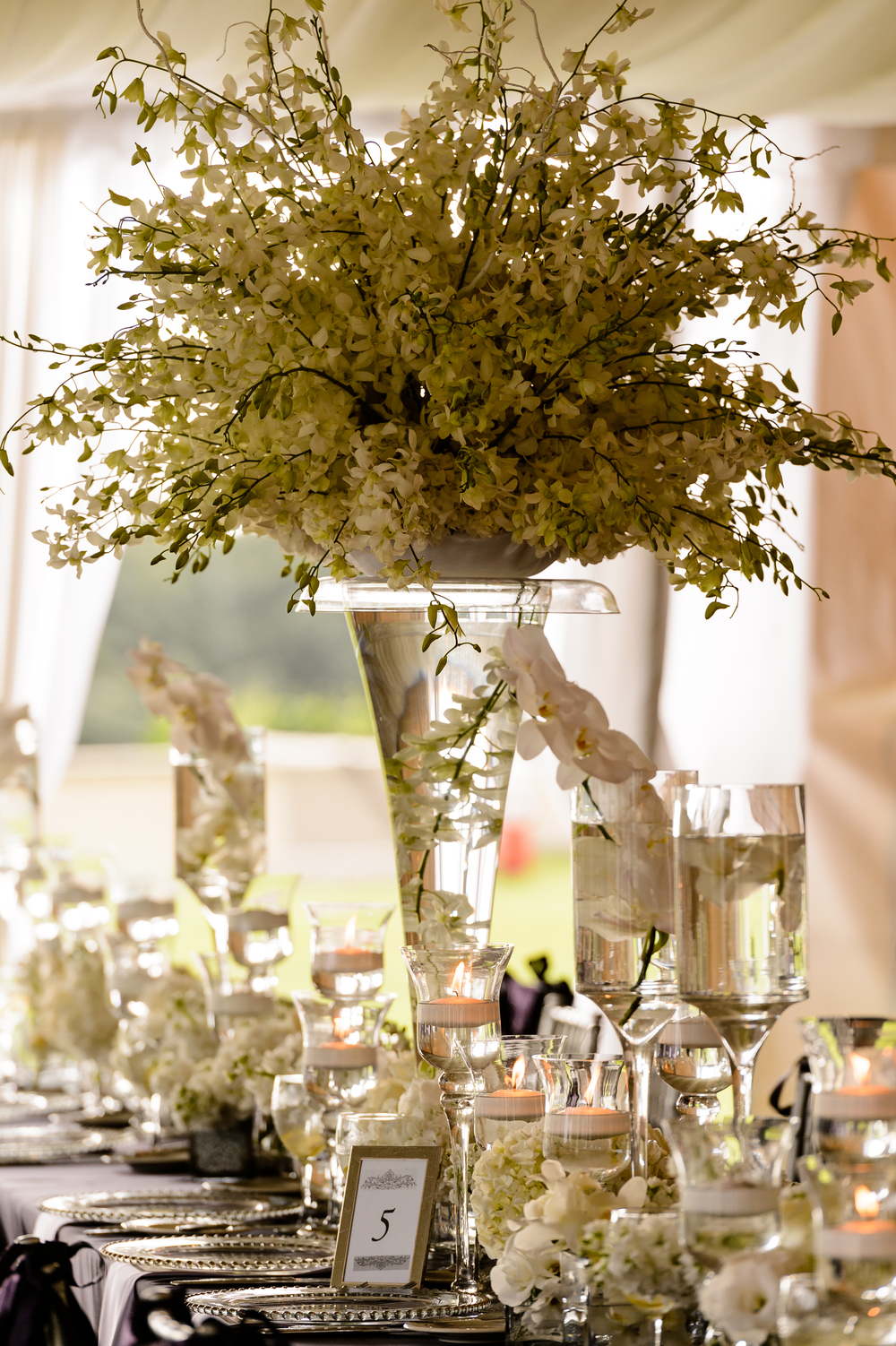 Grand Centerpieces of white orchids, multiple heights of candles, goblets with floating candles, white grouping of flowers, all different and giving texture to the feasting tables.