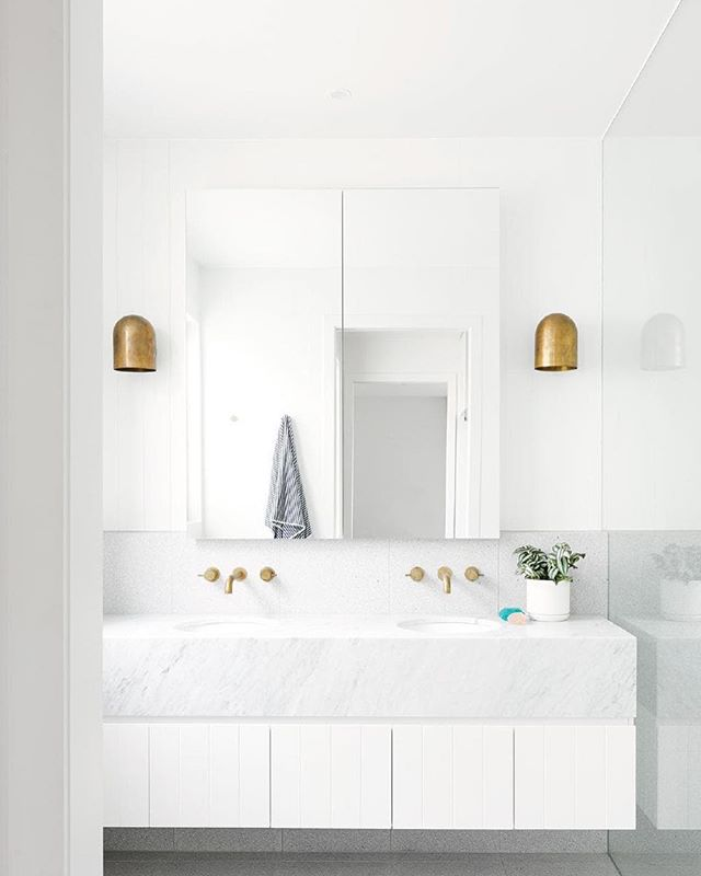 Featured recently in InsideOut magazine is this stunning family home in Geelong VIC. This beautiful and minimalist bathroom is flanked by a pair of our Duomo wall sconces in Whiskey brass. 🙏🏼 @emma_omeara 📷 @nikoleramsay .  #light #lighting #lightingdesign #Interior #interiordesign #contemporary #geometric #minimal #white #brass #⚡️ #💥