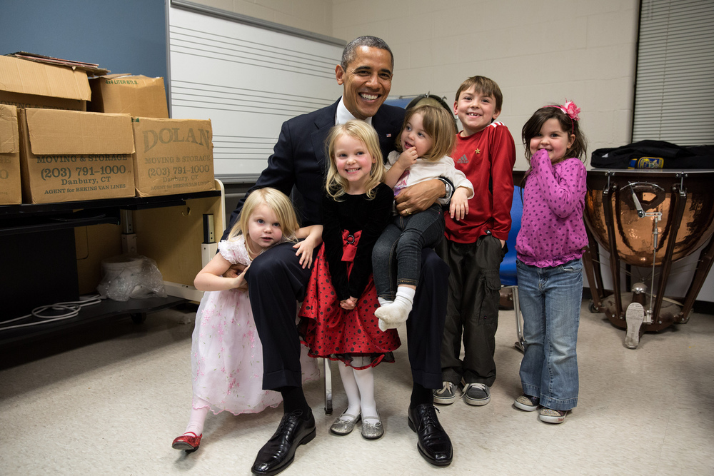 """Dec. 16, 2012   """"Two days after the shootings at Newtown, the President traveled to Connecticut to meet with the victims' families and give remarks at a prayer vigil. The President spent hours greeting family members. Difficult as that was for everyone, the one moment that helped sooth the pain was when he posed for a photo with the siblings and cousins of Emilie Parker, one of the 20 children who died that day in Newtown. I see both sadness and hope in this photograph, and I know after a lot of tears that day, it meant so much to the President that everyone was able to smile for a moment in this family photo. Thanks to the Parker family for allowing us to show this photograph publicly."""" (Official White House Photo by Pete Souza)"""