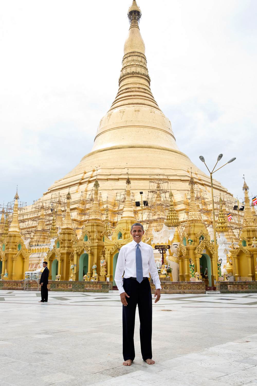 """Nov. 19, 2012  """"To some, this is just a snapshot and doesn't belong in this gallery of candid photographs from the year. But to me, it evokes what the trip to Burma was all about. Here is the President, shoes and socks off in respect, posing like an American tourist in front of the oldest pagoda in the world in a country that no U.S. President had ever been able to visit.""""President Barack Obama stands barefoot in front of the 368-foot tall Shwedagon pagoda in Rangoon, Burma, Nov. 19, 2012. (Official White House Photo by Pete Souza)"""