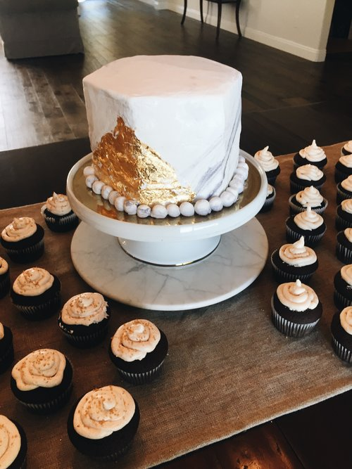 Chocolate cake with cinnamon honey buttercream, marbled marshmallow fondant and real gold leafing. And 150 chocolate cupcakes with frosting (Half cinnamon honey buttercream and half caramel buttercream with gold flakes on top.)