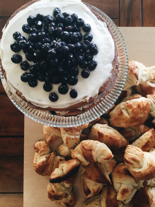 Maple breakfast cake with maple butter cream and topped with blueberries. Fresh baked croissants on the side.