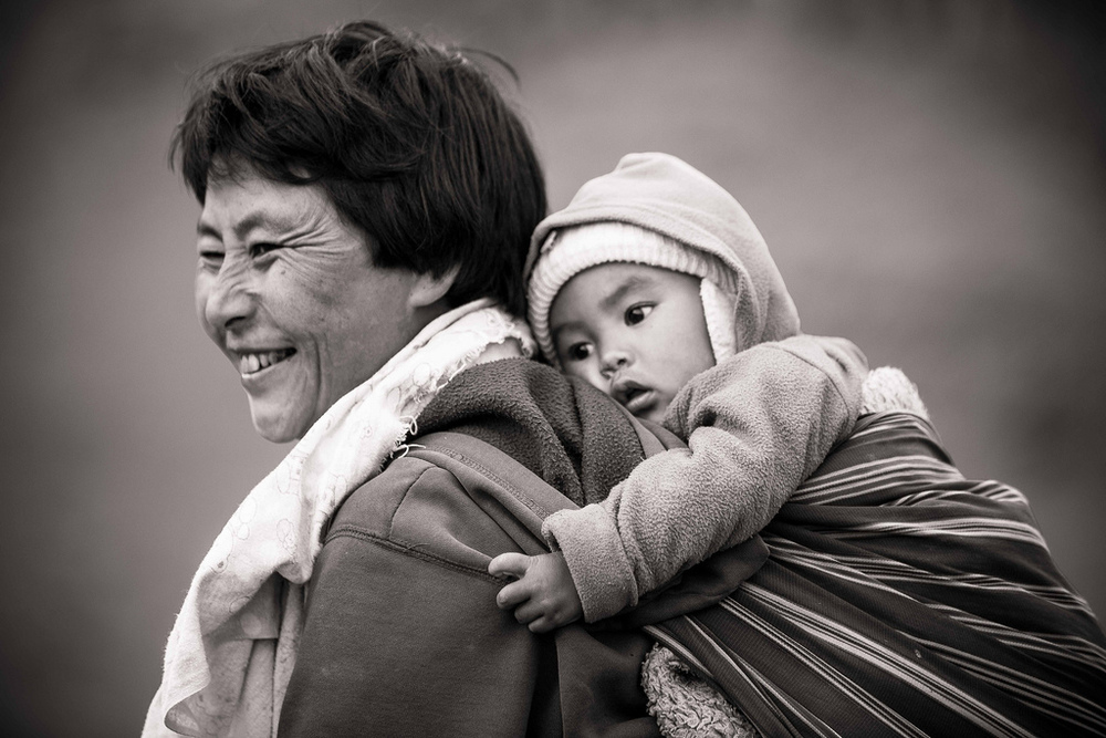 A mother carrying her child during the day's work // Ura Village, Bhutan // June 2012