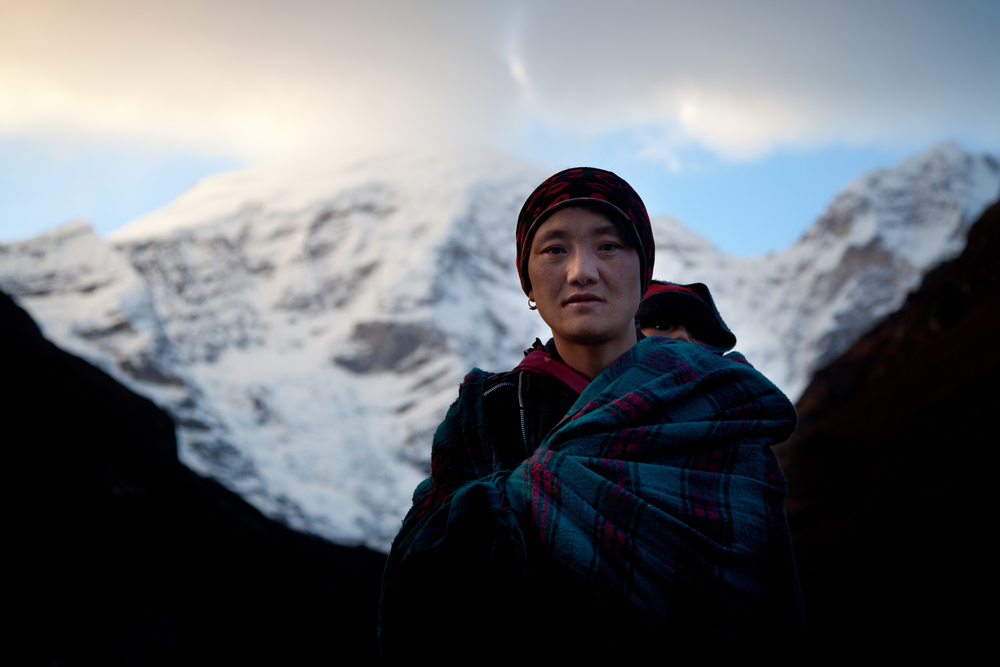 A women and her baby stand in front of Mt. Jomolhari, the tallest peak in Bhutan