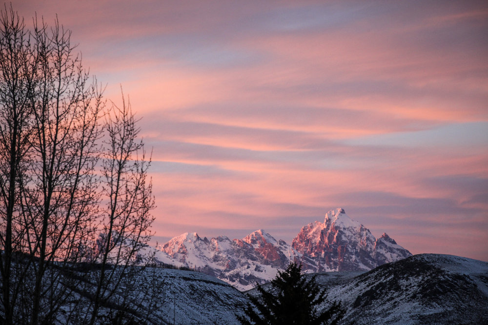 The sunset glows on the Teton Mountains as another day concludes in Jackson Hole, Wyoming, USA.